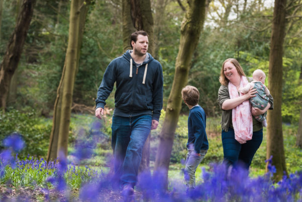 Family walking bluebell woods during spring photoshoot in Wallingford