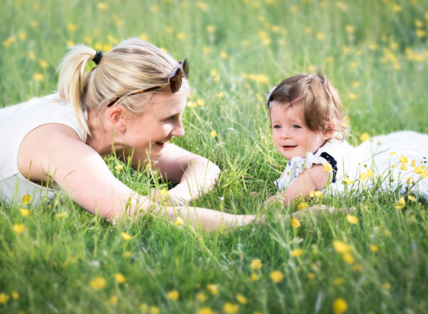 Mum and baby lying in buttercup meadow on photoshoot in Wallingford