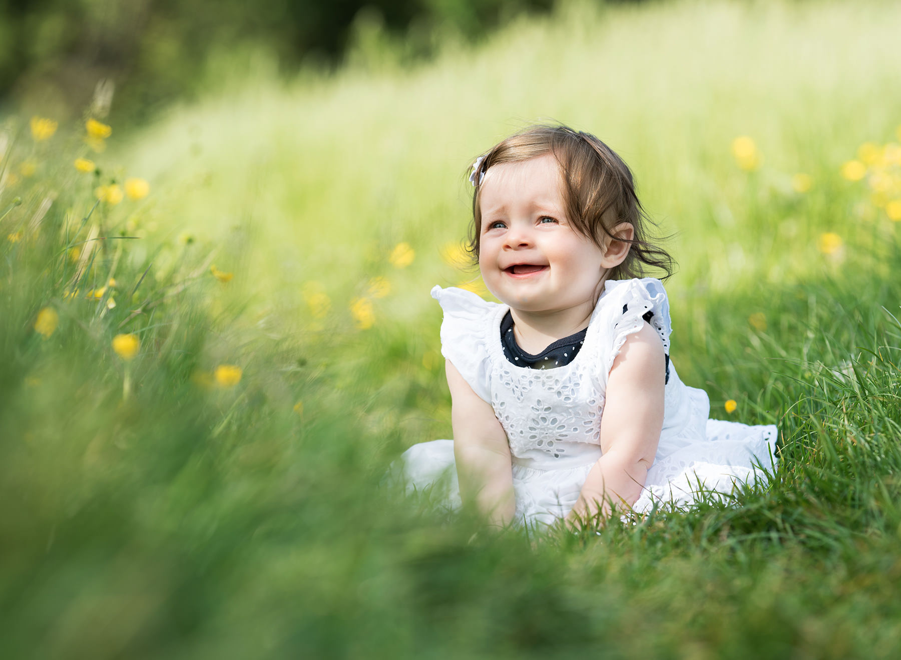 Baby smiling in buttercup meadow during spring photoshoot in Wallingford