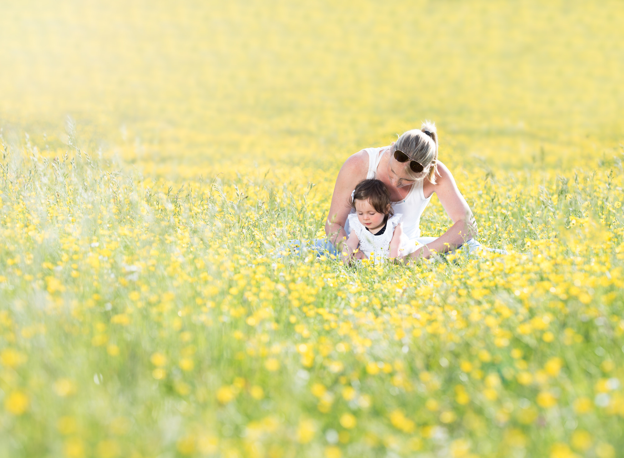 Mother and baby sit amongst a sea of buttercups during spring photoshoot in Wallingford