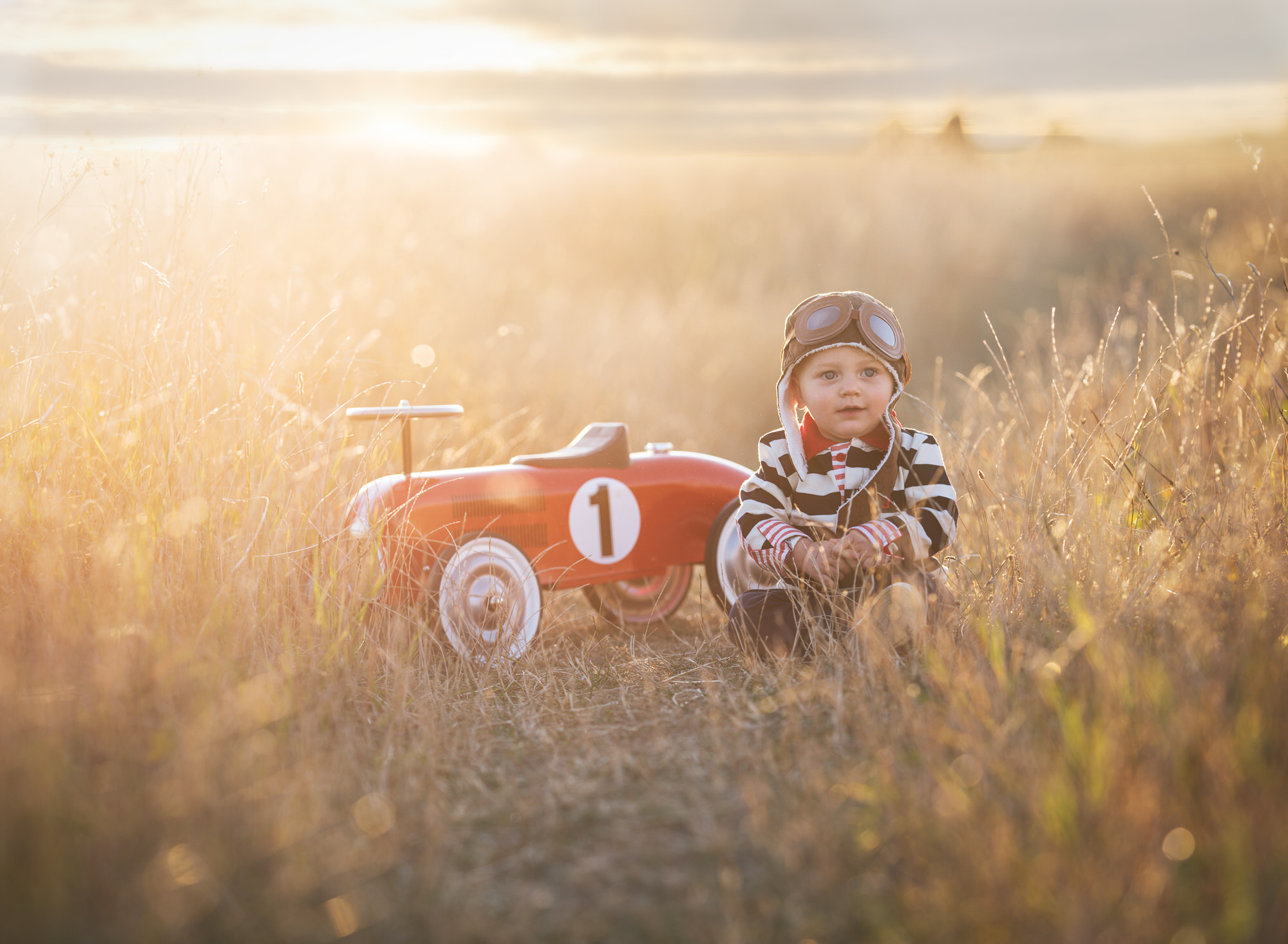Toddler boy sat with a vintage car at sunset during Benson Photoshoot