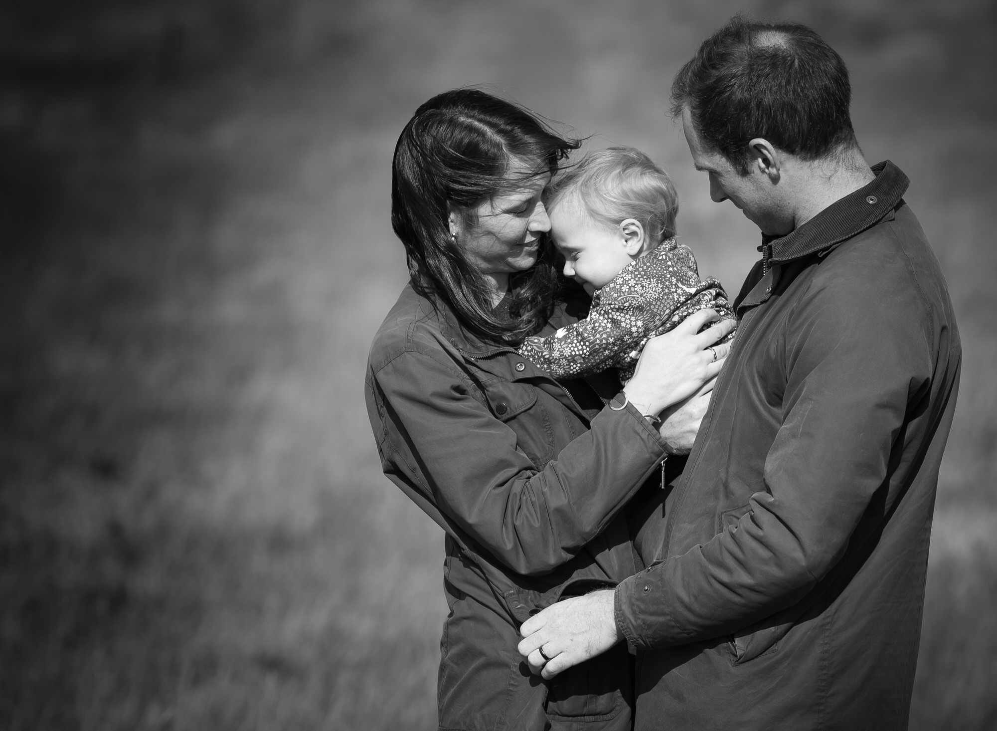 Family cuddle in a black and white image during photoshoot in Benson