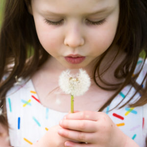 Girl blowing a dandelion during a Spring photoshoot in Wallingford