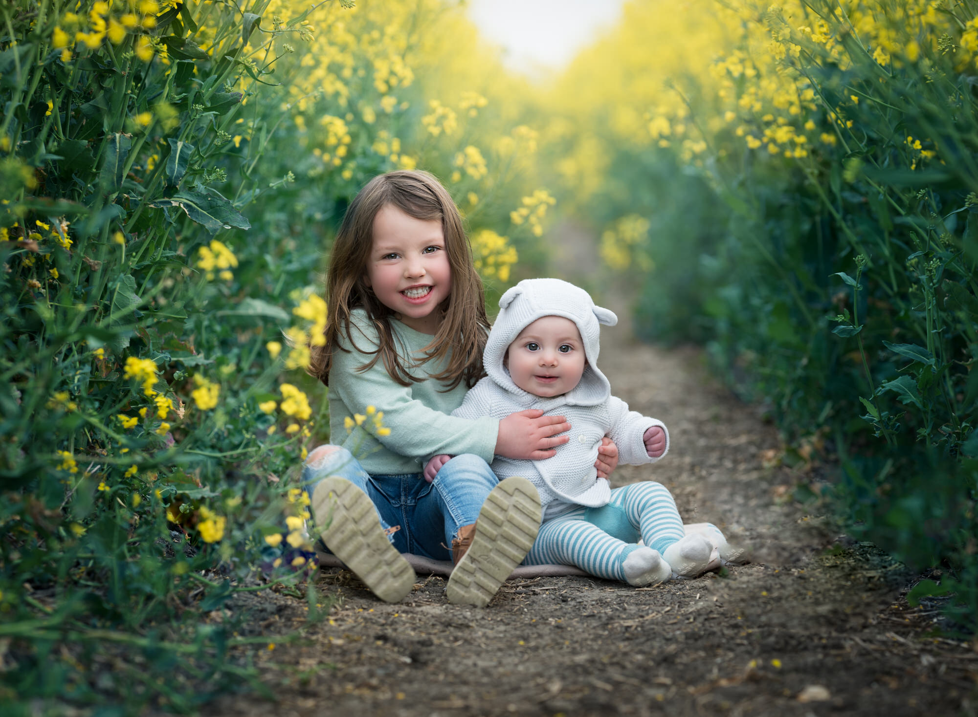 Sisters sit amongst the rapeseed during Spring photoshoot in Benson Wallingford