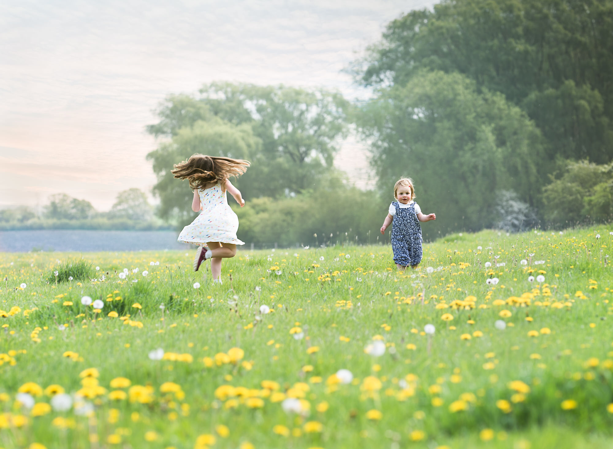 Sisters twirling in a field of dandelions at photoshoot in Wallingford