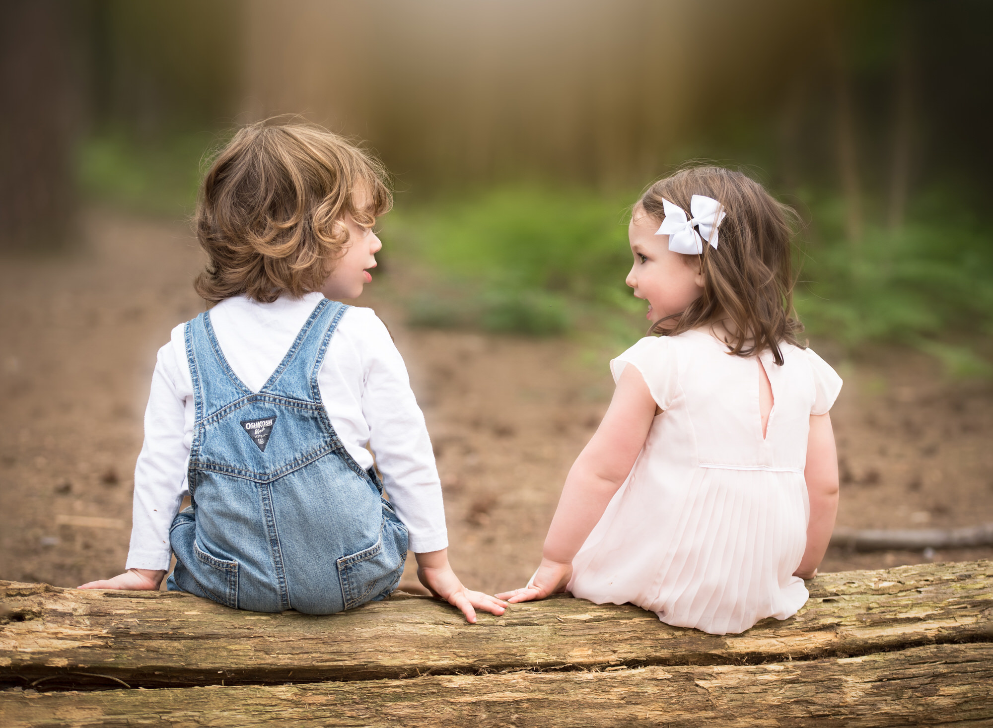 Girl and Boy looking at each other in woodland during photoshoot in Benson
