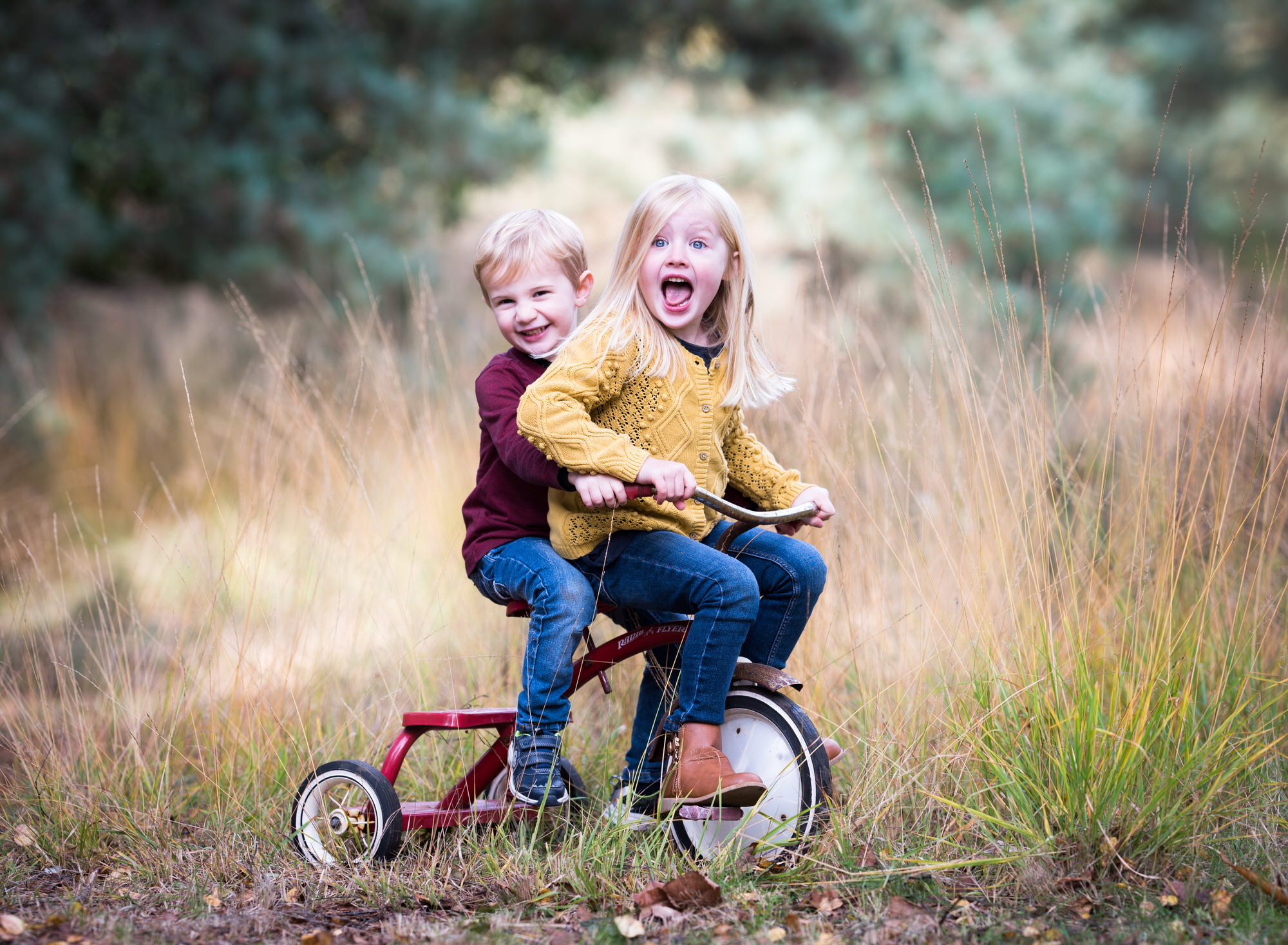 Siblings smiling on a tricycle during a photoshoot in Benson
